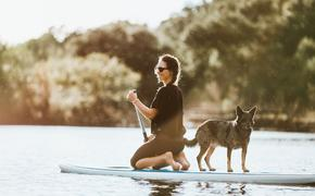 Woman paddle boarding with her dog in Austin, Texas
