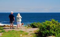 A couple and their pet take in the view of the Sea near Cape Elizabeth, Maine