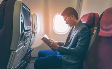 Man smiling and reading a book in airplane