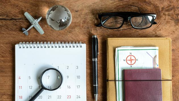 diary, map and calendar with passport (Photo via kitzcorner / iStock / Getty Images Plus)
