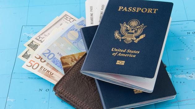 Passports and wallet with dollars, euro and credit card on a map background (Photo via volgariver / iStock / Getty Images Plus)
