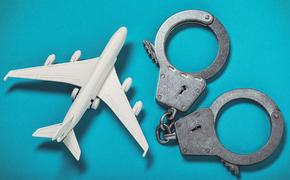 Airplane and handcuffs on the table.