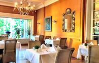 The breakfast room at the Atlantic Parkhotel in Baden-Baden Germany with white tableclothes and a chandelier