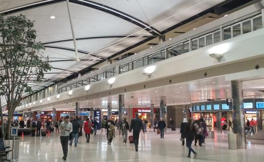 Travelers walking through a terminal at Detroit Metropolitan Airport