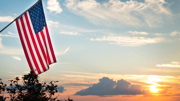 Bright american flag flying above beautiful sunset over Mississippi river