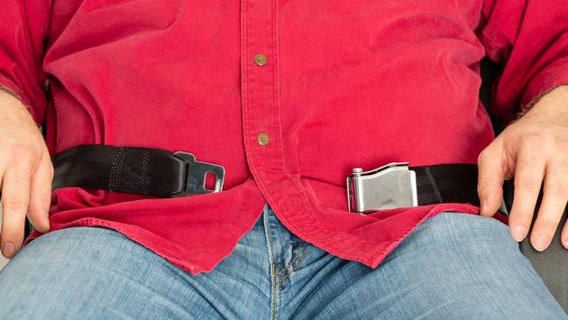 Overweight passenger unable to fasten seatbelt taking up both armrests