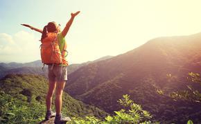 Woman celebrates reaching the mountain peak