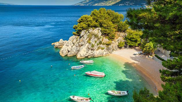 The Adriatic Sea, Biokovo mountains and majestic bay surround Brela Beach in Croatia.