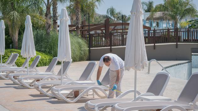 Resort employee measures the distances between poolside lounge chairs.