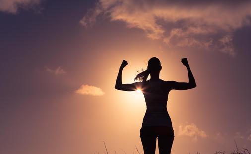 A confident woman flexing in achievement
