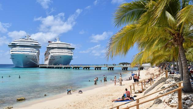 Carnival Cruise ships docked side-by-side in the Caribbean.