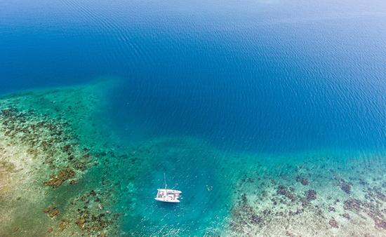 A catamaran anchored near a tropical coral reef in Belize