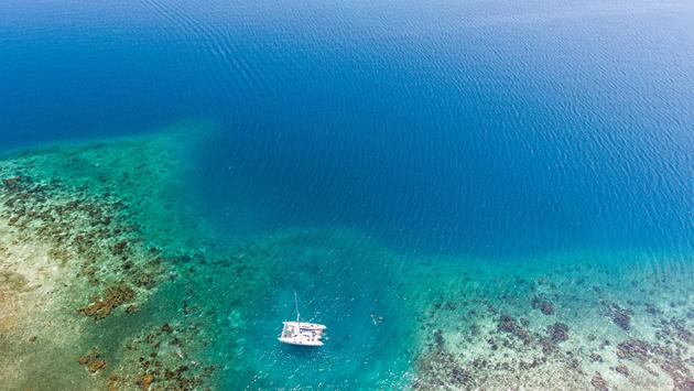 A catamaran anchored near a tropical coral reef in Belize