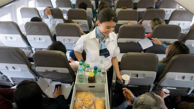 Flight attendant serving food and beverages to passengers.