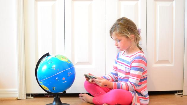 child looking at globe, learning about geography