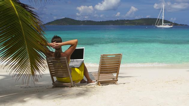 Woman sitting on the beach with her laptop in St. John, US Virgin Islands.