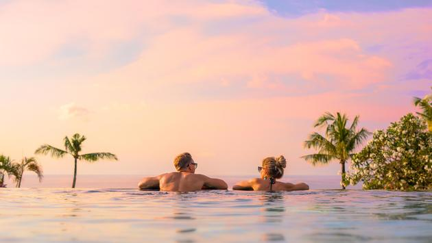 Couple looking at beautiful sunset in infinity pool