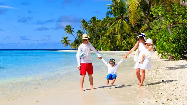 family with two kids playing on beach