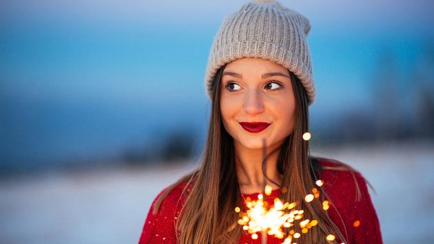young woman holding a sparkling stick (Photo via bernardbodo / iStock / Getty Images Plus)