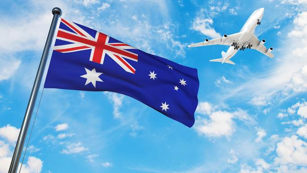 The Australian national flag with a plane flying overhead.