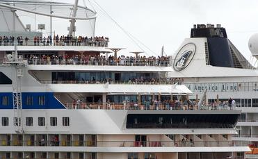 Passengers mass on the rear deck of a cruise ship as it leaves the harbor