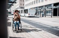 Woman in a wheelchair waiting on the bus