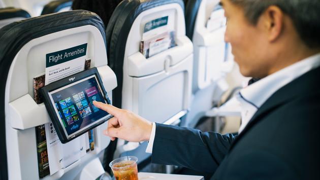 Alaska Airlines passenger using entertainment tablet