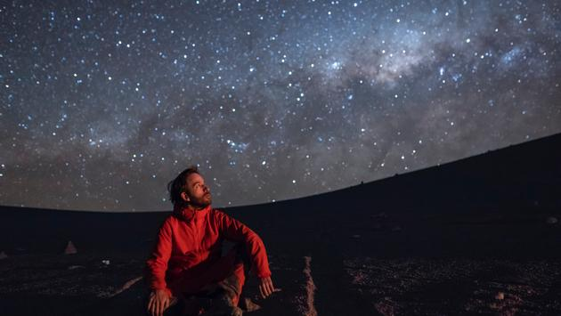Man observing the Milky Way galaxy in the Atacama Desert, Chile.