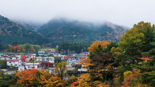 Morning scenery of village surrounded with colorful autumnal trees in Kinugawa onsen area of Nikko, Japan