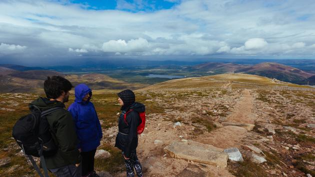 Three hikers stand at the peak of CairnGorm mountain in Scotland