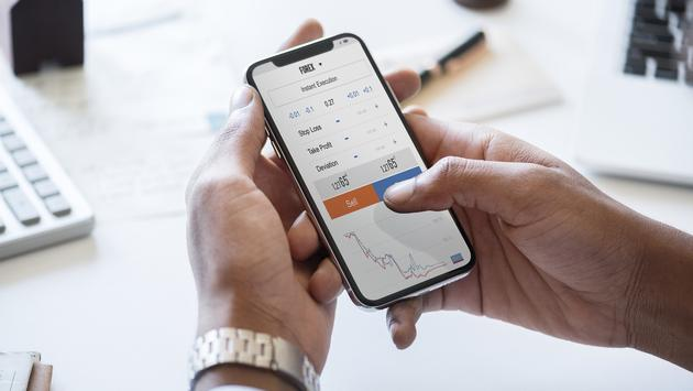 Businessman checking stock market on smartphone