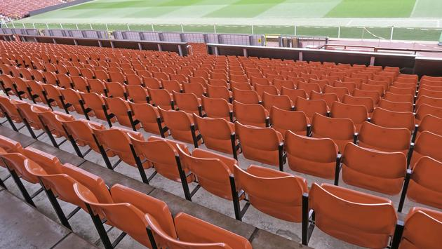 The red stadium seats of Old Trafford in Manchester, England