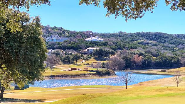 Golf course with glittering lake and oak trees