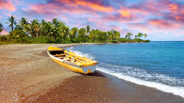 Wooden fishing boat on beach at sunset in Jamaica.