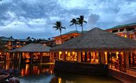 Sunset view of overwater hut restaurant with palm trees