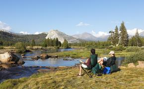 A couple relaxing on the banks of the Tuolumne River in Yosemite National Park, camping