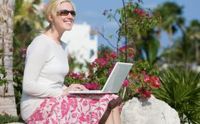 Woman working remotely in a tropical outdoor setting.