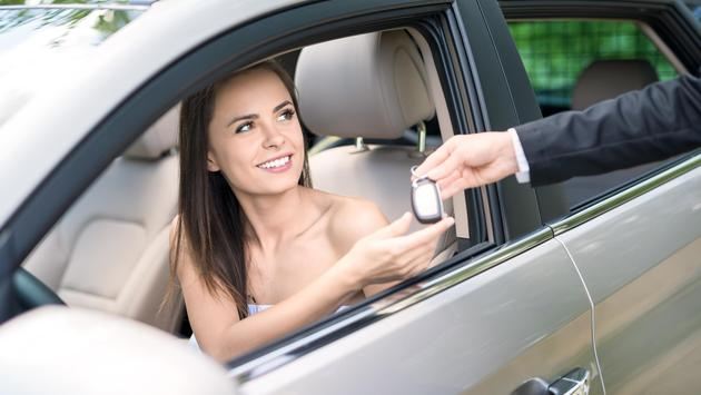 Woman receiving the keys to a rental car