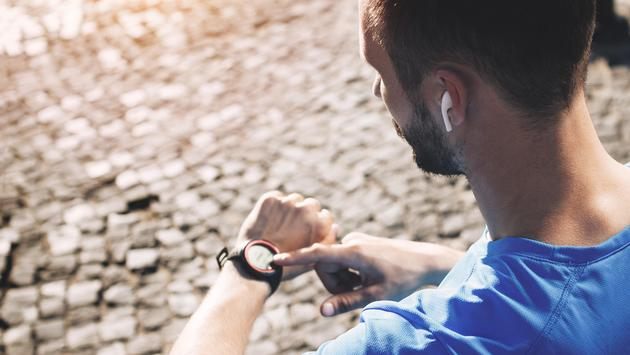 Man training with wireless headphones and smartwatch