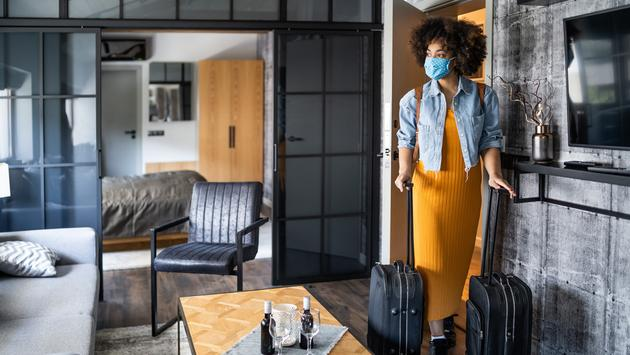 Women entering hotel room during COVID-19 pandemic.