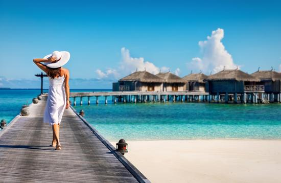 Woman in white walking over a wooden jetty in the Maldives (Photo via SHansche / iStock / Getty Images Plus)