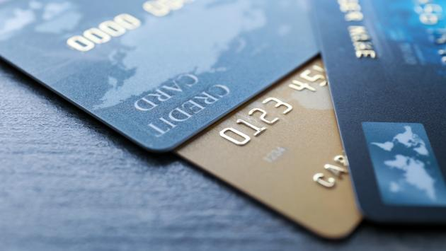 Different credit cards on table, closeup (Photo via belchonock / iStock / Getty Images Plus)