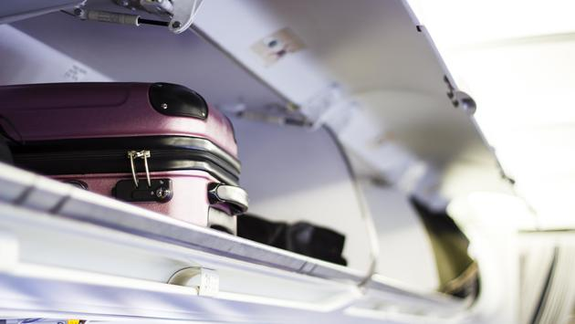 A suitcase in the overhead bin