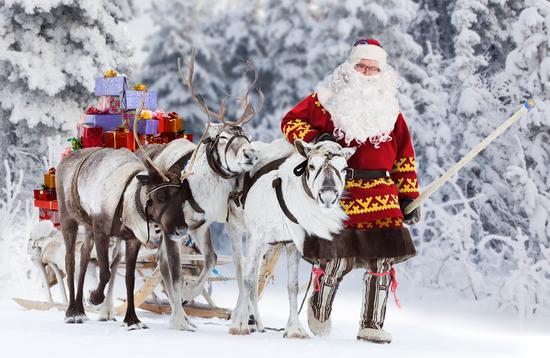 A Santa Claus with his reindeer and sleigh.