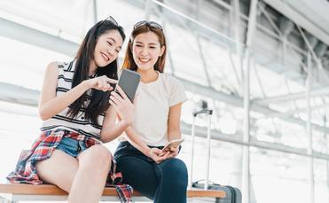 Girls using smartphone checking flight