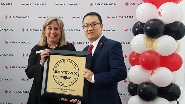Lucie Guillemette, Air Canada CCO, and Andrew Yiu, Air Canada vice president of Product, hold the airline's 2018 Skytrax award for Best Airline in North America.
