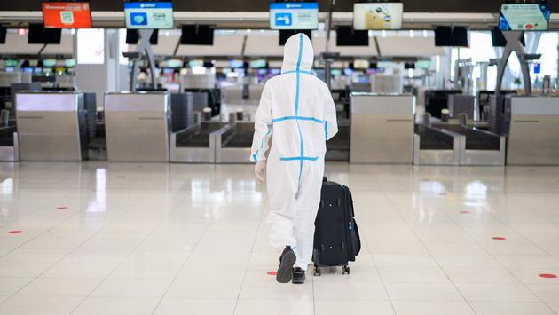 Man wearing PPE suit at the airport