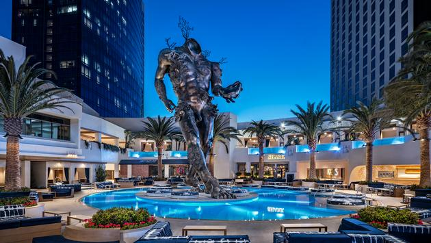 Damien Hirst's 'Demon with Bowl' sculpture rises up from KAOS' outdoor pool complex, Palms Casino Resort