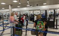 Travelers wait in the security line at the airport