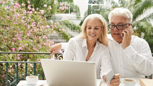 Senior couple on the phone and computer (Photo via DragonImages / iStock / Getty Images Plus)